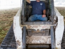 David Lindstrom in the cab of his Bobcat dozer during the tent raising.