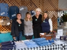 Leona Walden and Sally Stewart with two other volunteers in the festival merchandise booth.